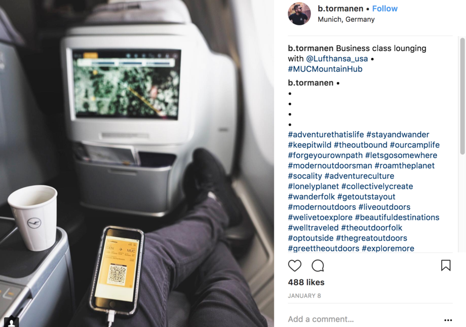 View of what a business class traveller sees - outstretched legs, computer, drink-holder. Comments to the right.