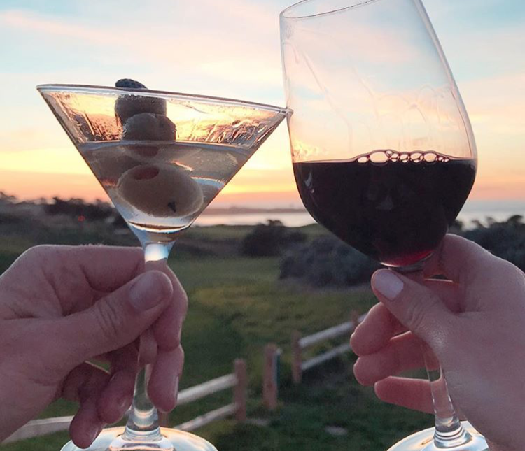 Glass of wine and martini hold together at sunset at The Inn at Spanish Bay.