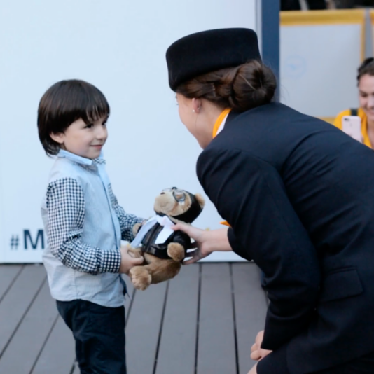 Flight attendant giving teddy bear to little boy.